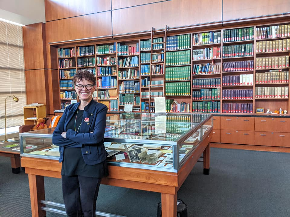 Micaela Sullivan-Fowler standing in front of a glass display case and bookshelves