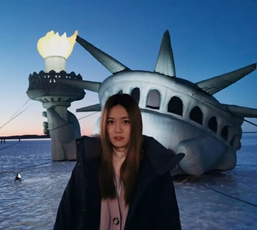 Photo of Runyi Wang in winter on Lake Mendota in front of a statue of Lady Liberty emerging from the ice