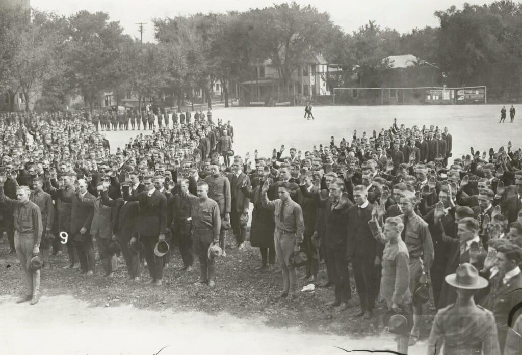 Large group of men in suits and military uniforms raising their right hands