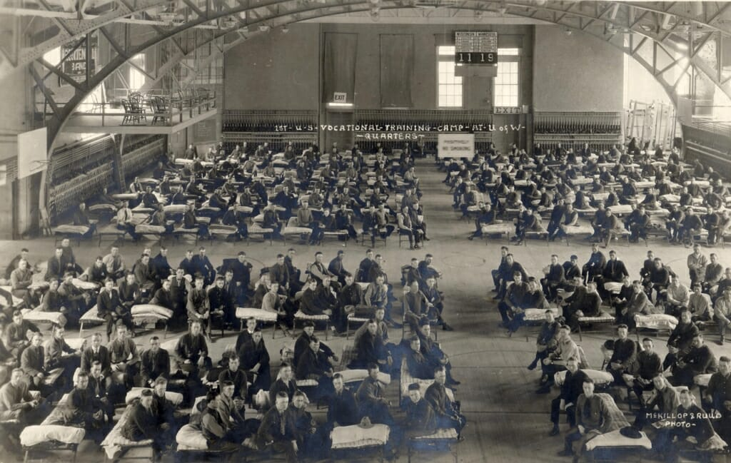 Dozens of cots with men in military uniforms sitting on them in large room with arched ceiling beams