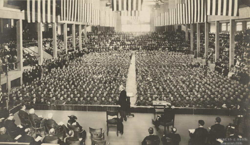 Charles Van Hise standing at podium before an audience of hundreds seated on the floor of the Stock Pavilion