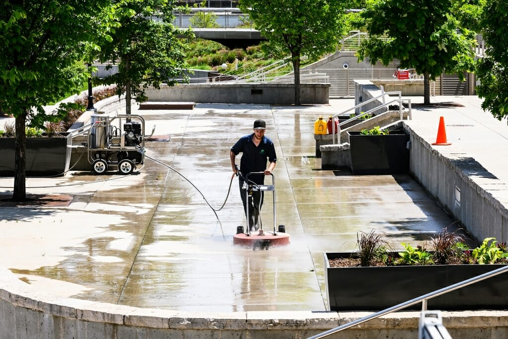 A lone worker scrubs an empty Terrace with a power-washing machine.