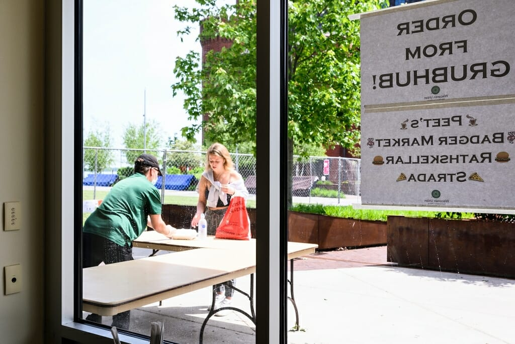 A worker behind a table gives food to someone arriving for pickup.