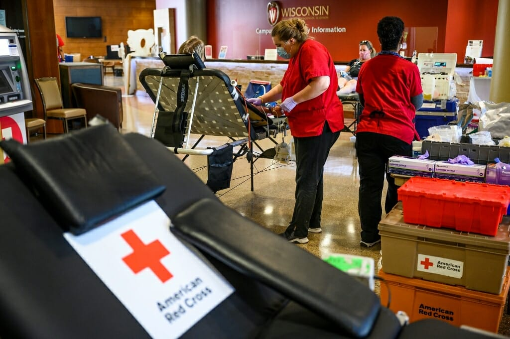 Red-clad Red Cross workers assist a blood donor.