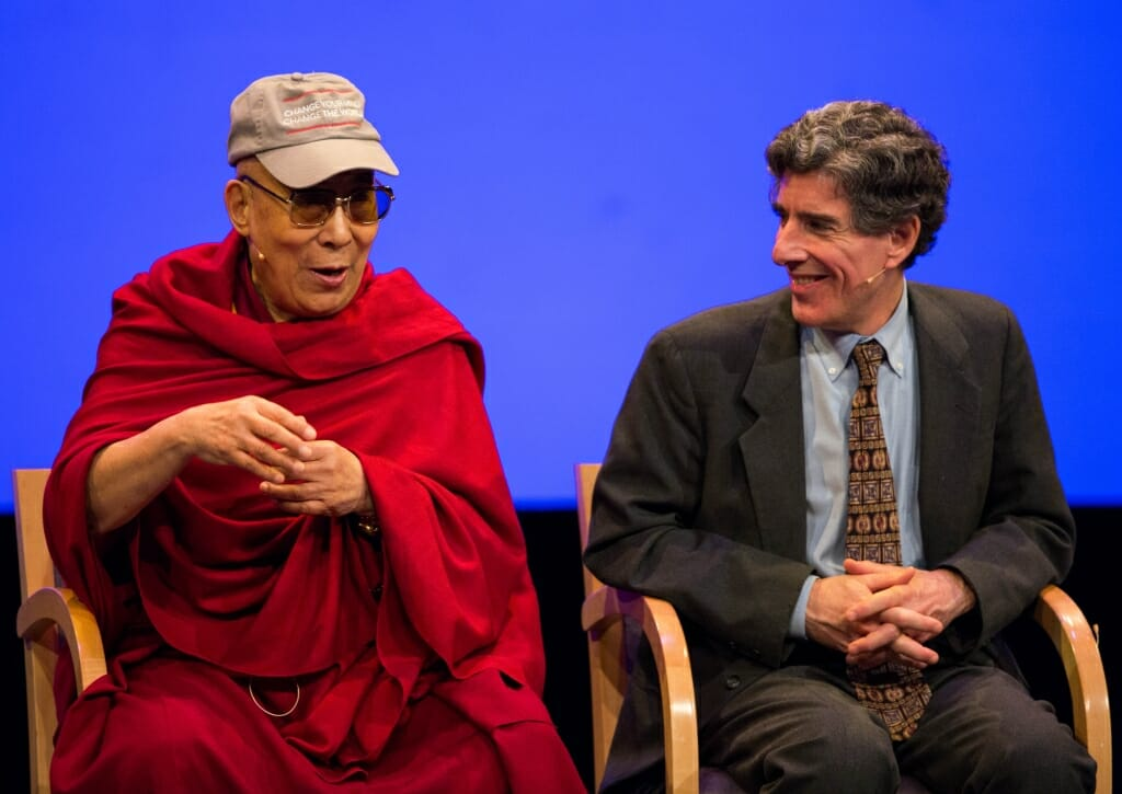 The Dalai Lama wearing a red robe sits next to Richard Davidson who is wearing a suit.
