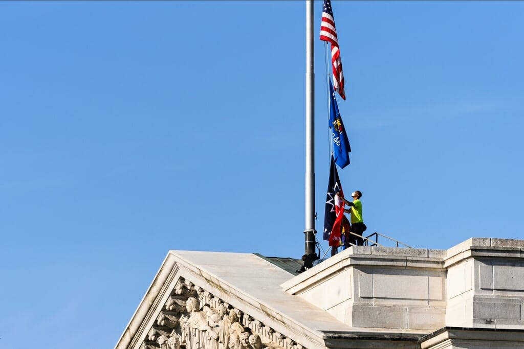 A worker standing on the roof of the State Capitol raises the Juneteenth flag along with the American and state flags.