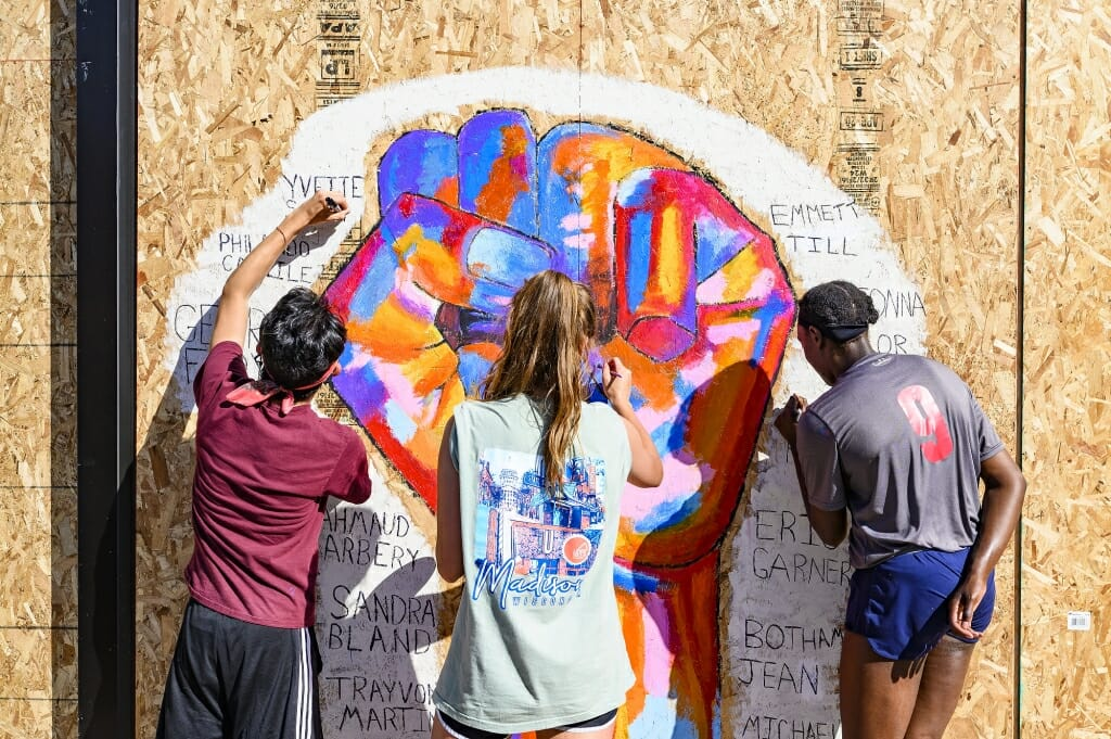 UW-Madison students (left to right) Daniel Ledin, Molly Pistono and Courtney Gorum work together to paint a mural commemorating the names of black victims of police violence throughout the country on a sheet of plywood covering the windows of the Community Pharmacy building on State Street in Madison June 5. The mural is one of many that have been painted on businesses and shops along the street following several nights of protests in response to the killing of George Floyd in Minneapolis.