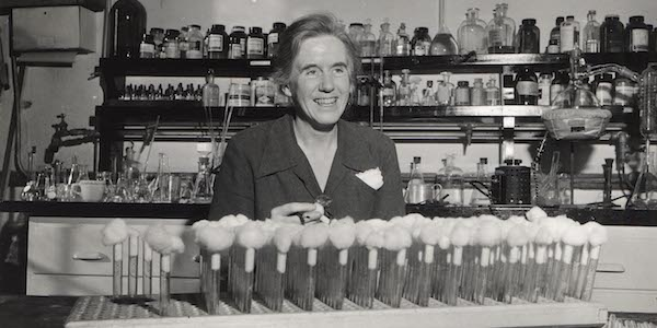 Elizabeth McCoy seated at a lab bench behind test tubes and in front of bottles and jars on shelves