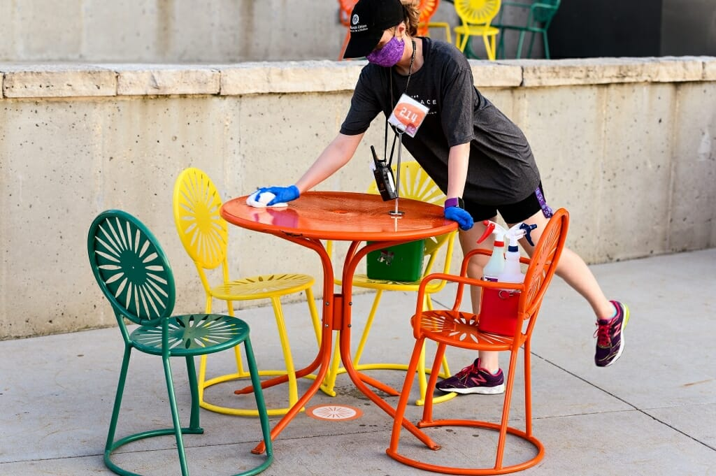 A person cleans off an orange Terrace table.