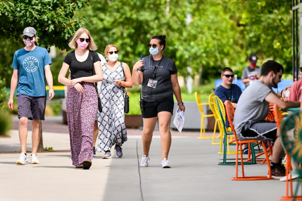 People wearing face masks are lead into the Terrace by a hostess also wearing a face mask.