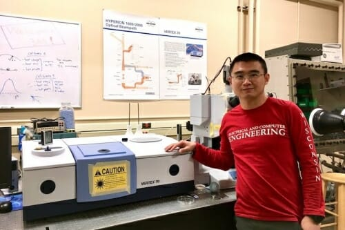 Yuzhe Xiao standing in front of a spectrometer
