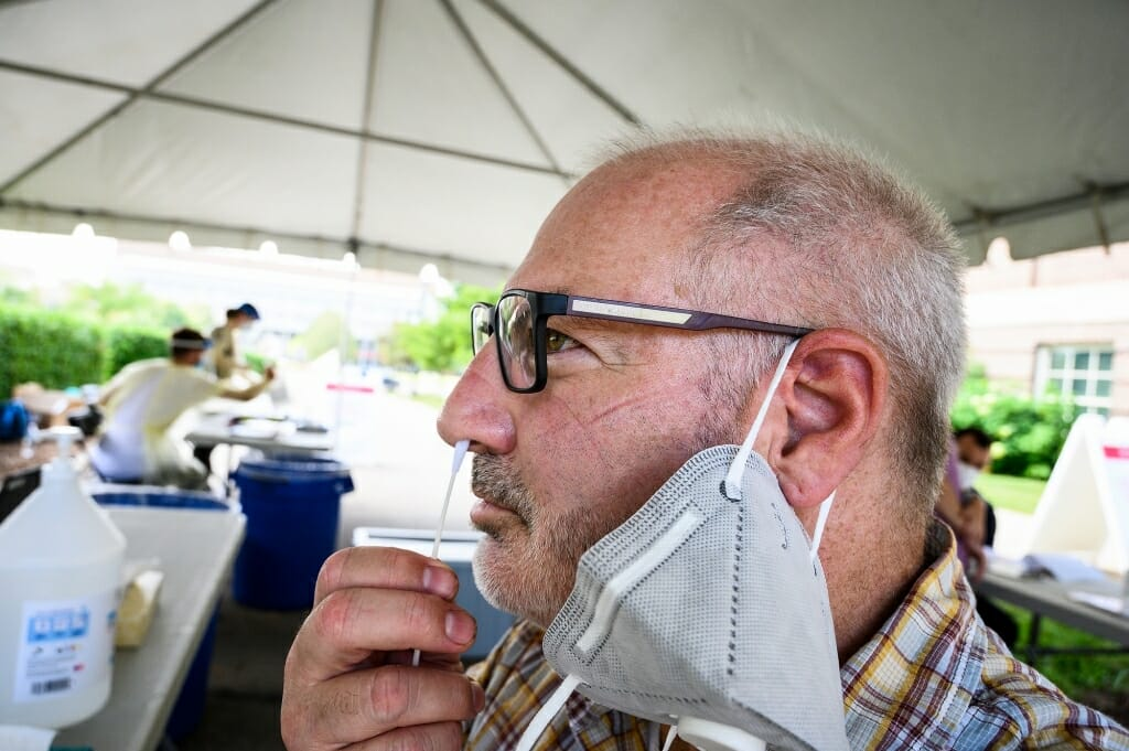 After receiving instruction from University Health Services staff, Jeff Miller, senior photographer in University Communications, self-administers a nasal-swab test at a COVID-19 testing tent.