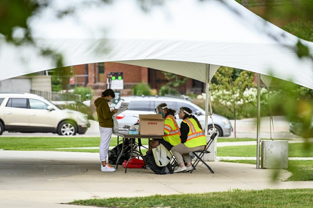 Poll workers wearing personal protective equipment help voters during an early in-person absentee voting session held on Library Mall.