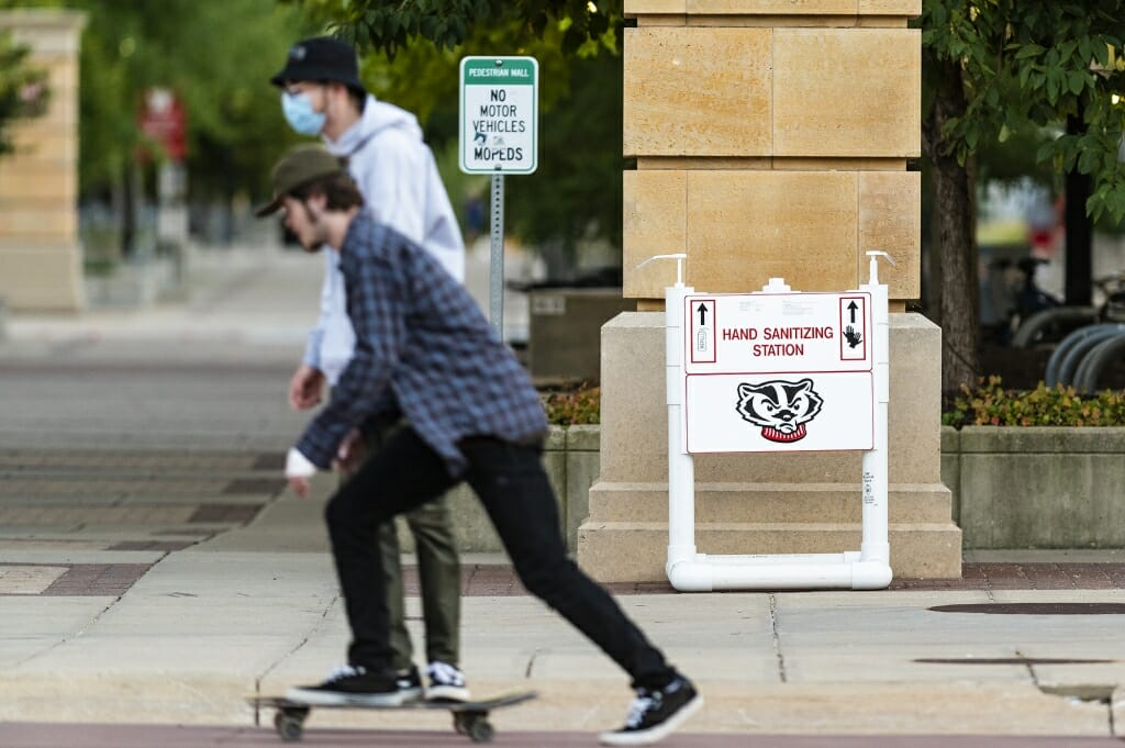 Pedestrians near 333 East Campus Mall pass by a newly installed hand sanitizer.