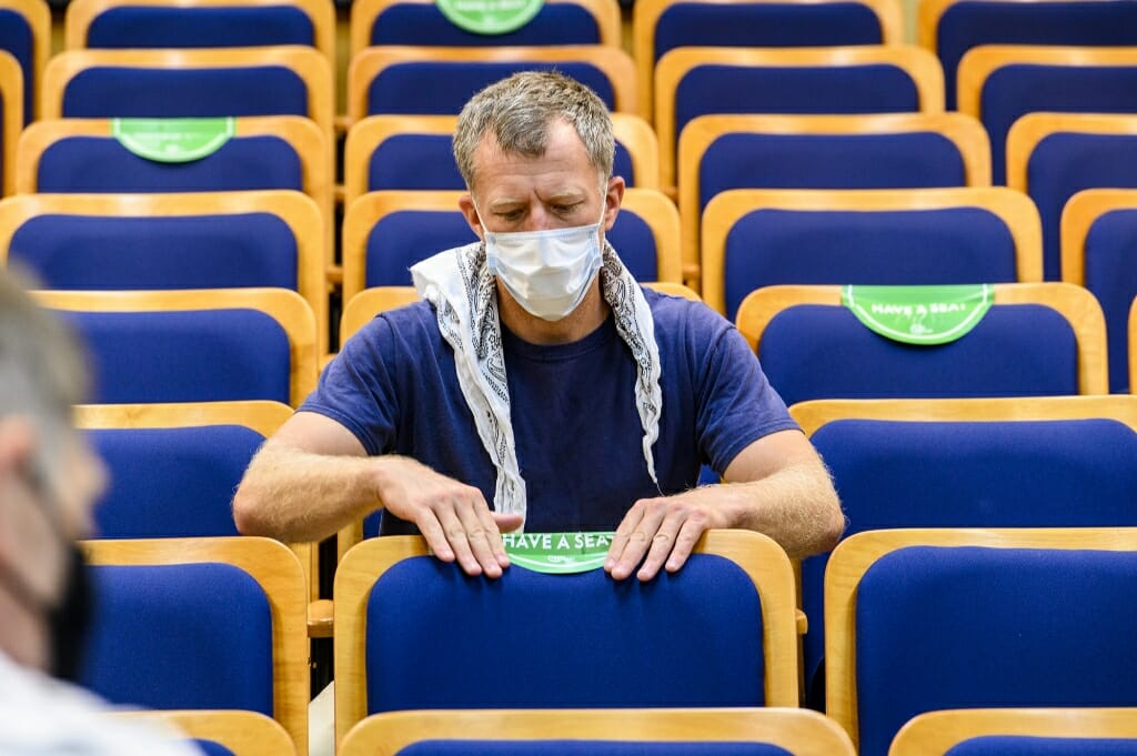 Staff member Donovan Kron places a seating location sticker on a seat back in a reconfigured lecture hall.