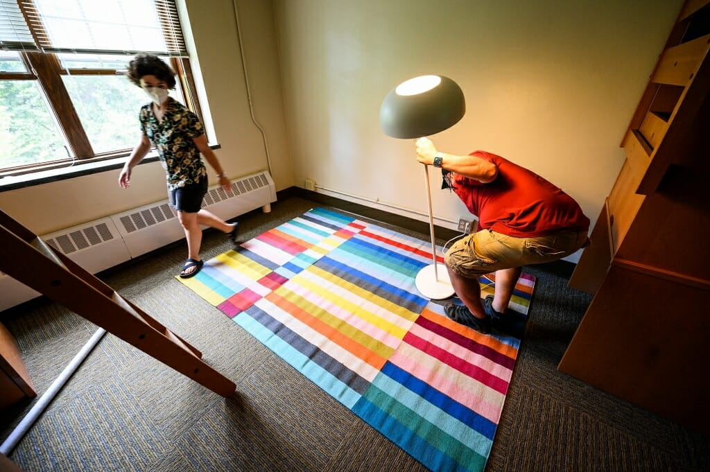 A brightly colored rug and a lamp add a touch of home to Bella Rosenberg's residence hall room.