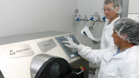 Photo of two staff members in protective lab gear standing next to a large centrifuge.