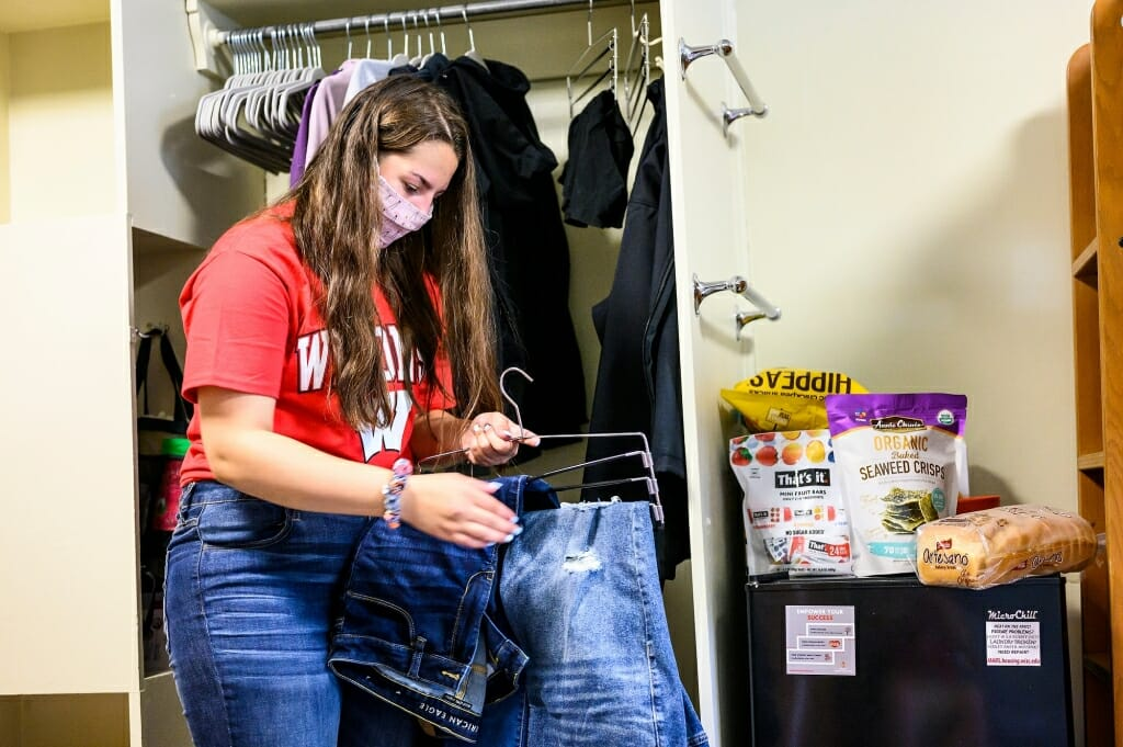 Maggie Chrostowski, a student from the Village of Hollandale, hangs clothes as she moves in to Elizabeth Waters Residence Hall.