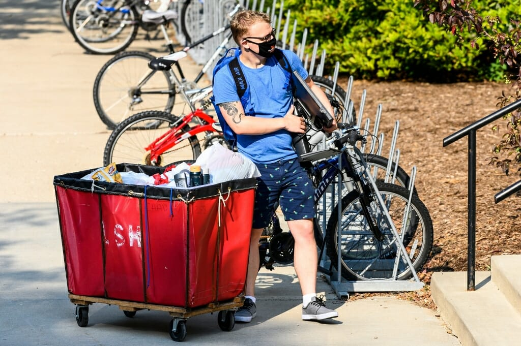 A student unloads a cart while moving in to one of the lakeshore residence halls.