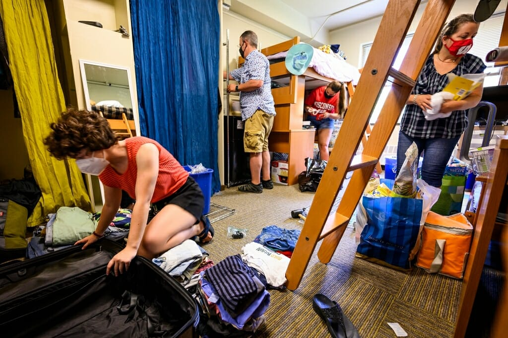 Student Bella Rosenberg, left, from Chicago, unpacks as her parents Todd Rosenberg and Stacey Raube help her move in to Elizabeth Waters Residence Hall.