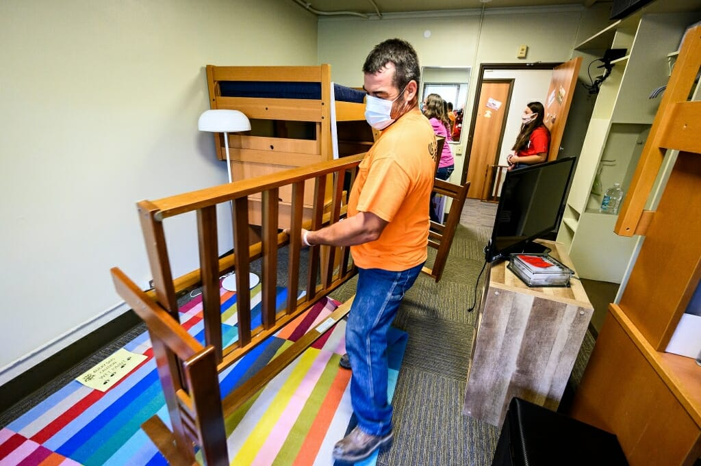 Mark Chrostowski carries a futon frame as he and wife Vicki help their daughter Maggie Chrostowski, standing in the doorway, move in to Elizabeth Waters Residence Hall.