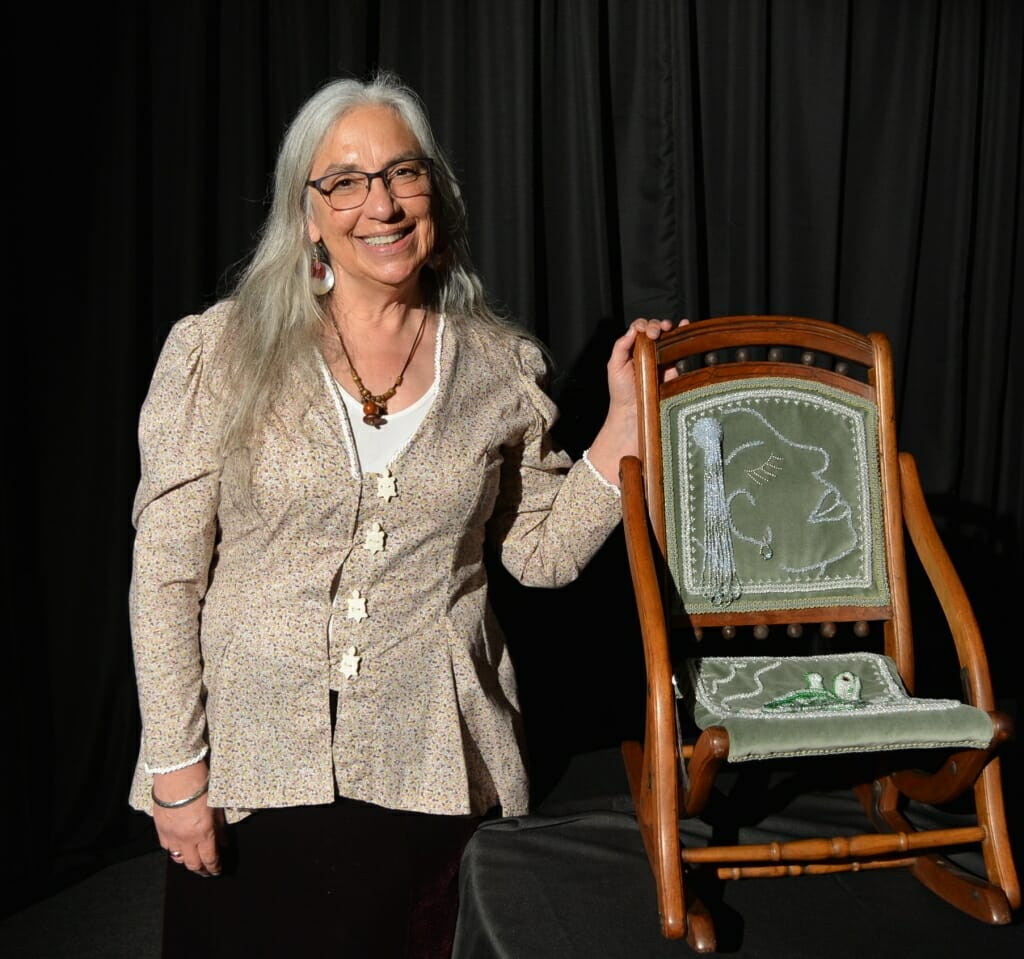 A woman stands next to a beaded chair.