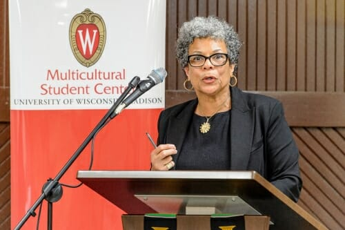 Adell speaking into a microphone at a podium