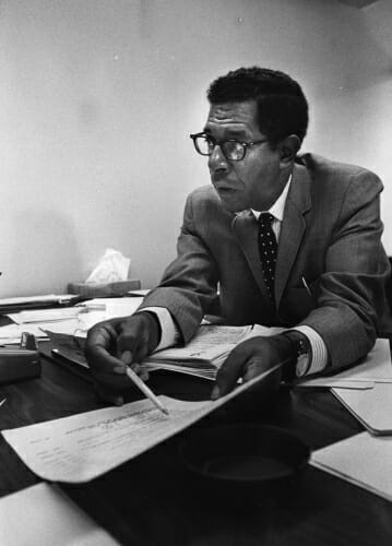 Anderson sitting at a desk pointing at a piece of paper