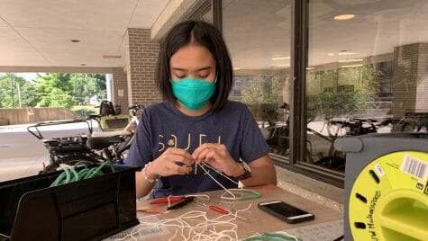 Student sitting at table assembling mask fitter