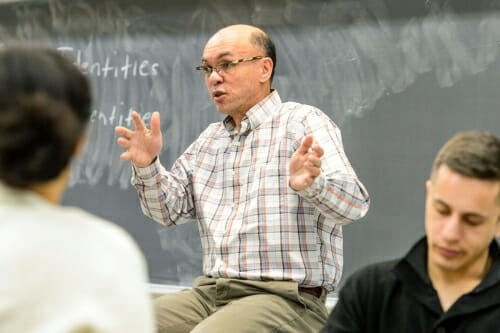 Thornton sitting in front of a chalkboard, gesturing and speaking