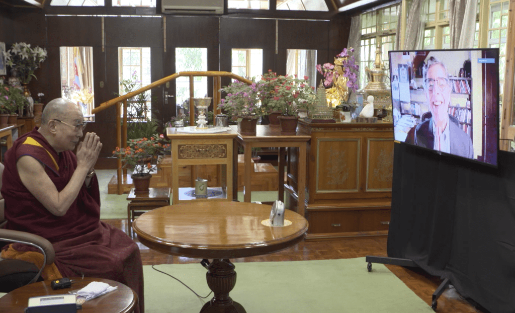 Dalai Lama sitting in a chair conversing with Richard Davidson on a video screen