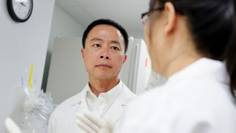 Su-Chun Zhang in his lab listening to a researcher