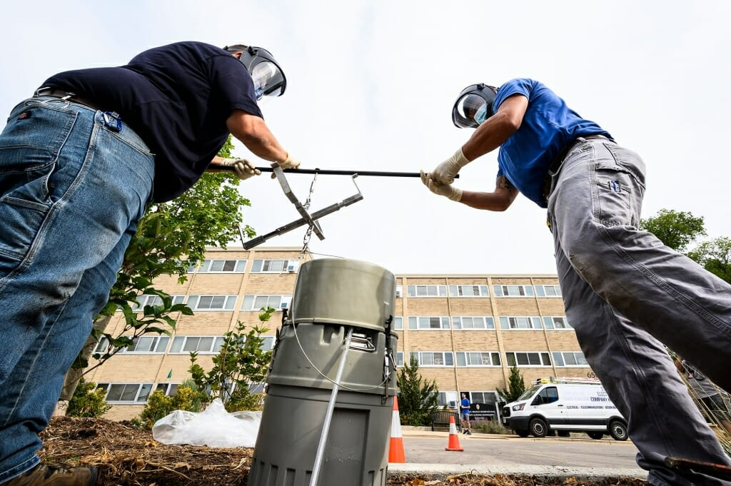 Two plumbers lifting a large cylinder out of a maintenance hole in front of a residence hall