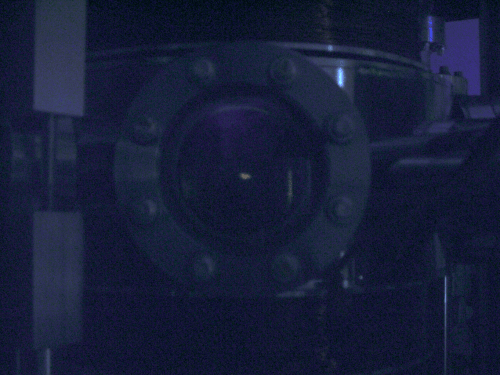 The chamber in the dark shows faintly glowing rubidium atoms at the center