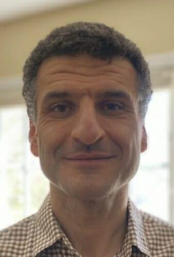 Portrait of Deniz Yavuz in front of a window