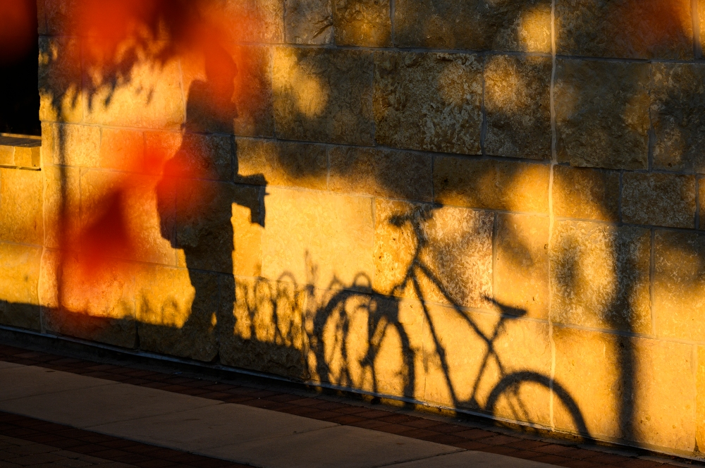Late afternoon shadows of a parked bike and a passing pedestrian are cast upon the stone exterior of the Gordon Dining and Event Center.