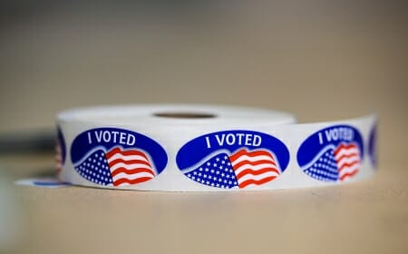 """Roll of oval """"I VOTED"""" stickers with American flags on them"""
