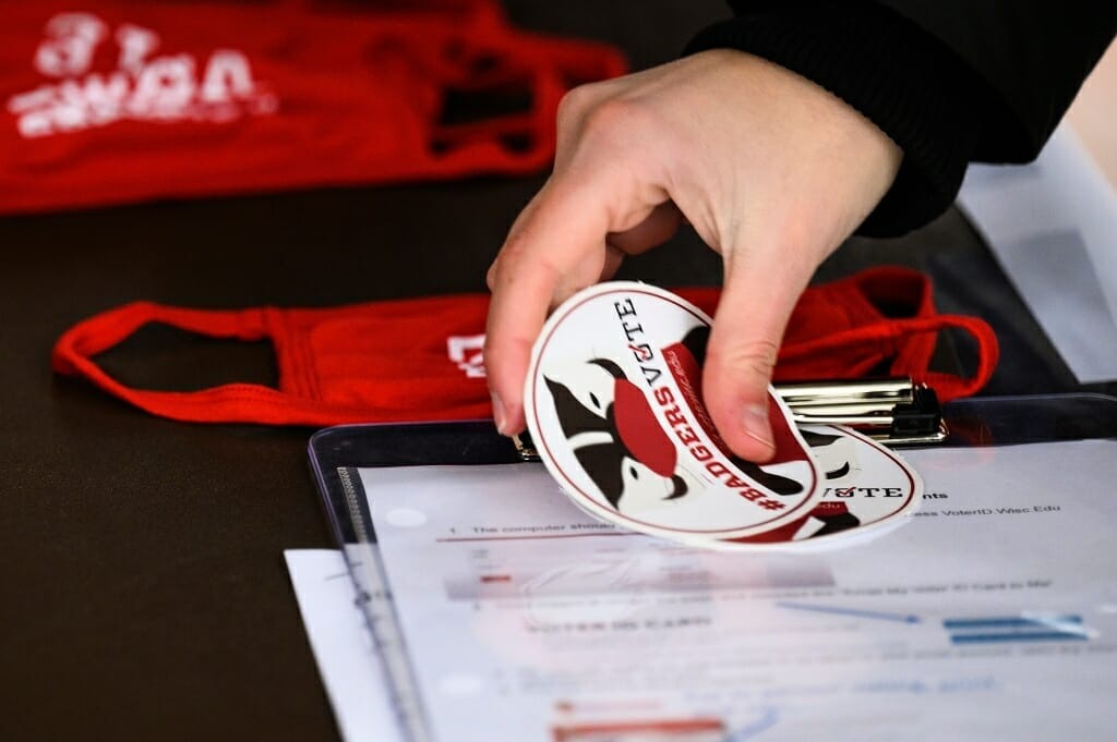 A student collects a #BadgersVote sticker after casting a vote.