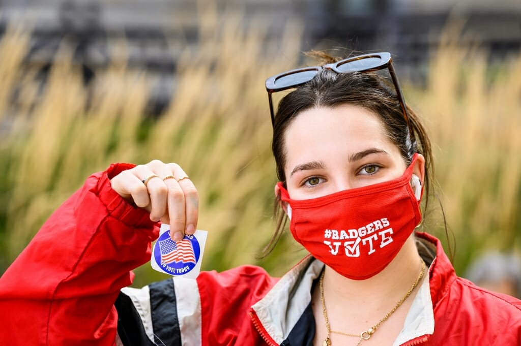 Maddie Stein, a first-year student from Los Angeles, shows a sticker and Badgers Vote mask after registering to vote with City of Madison Clerk's Office staff working an information table on East Campus Mall.