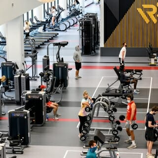 Students lift weights and work out in the strength equipment area.