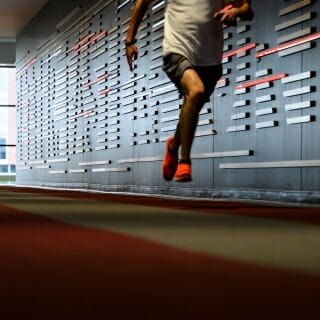 A student sprints while running along the indoor track.