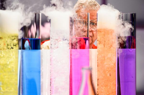 Shakhashiri's face behind beakers of colorful liquids