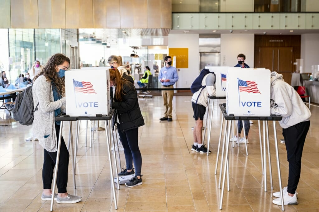 Students cast their ballots in physically distanced voting booths at the Chazen Museum of Art polling station.