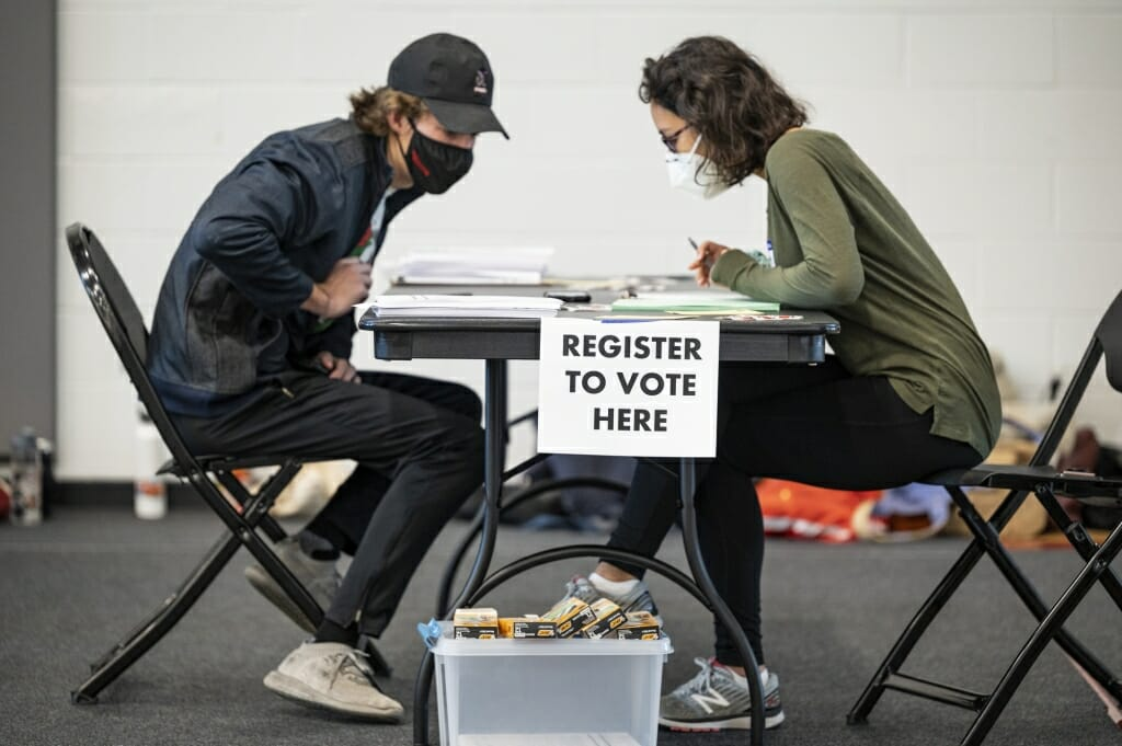 A poll worker helps a student register to vote at the Nicholas Recreation Center polling station.