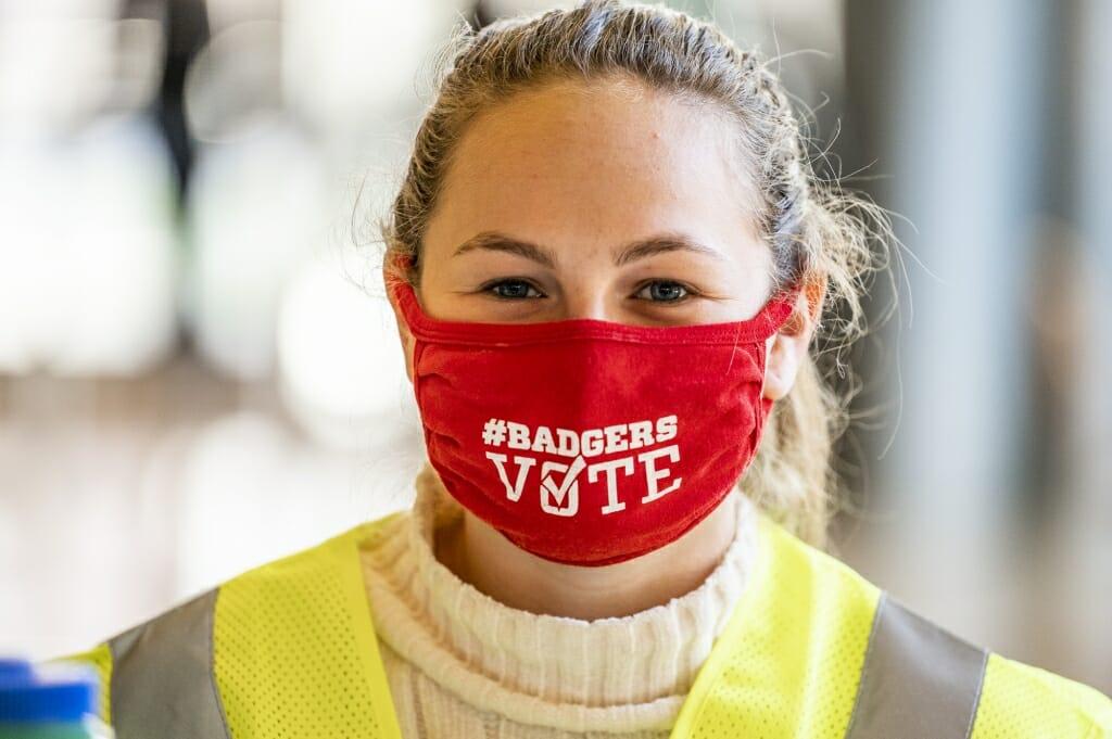 UW student volunteer election worker Elise Goldstein shows off the voting message on her face mask.
