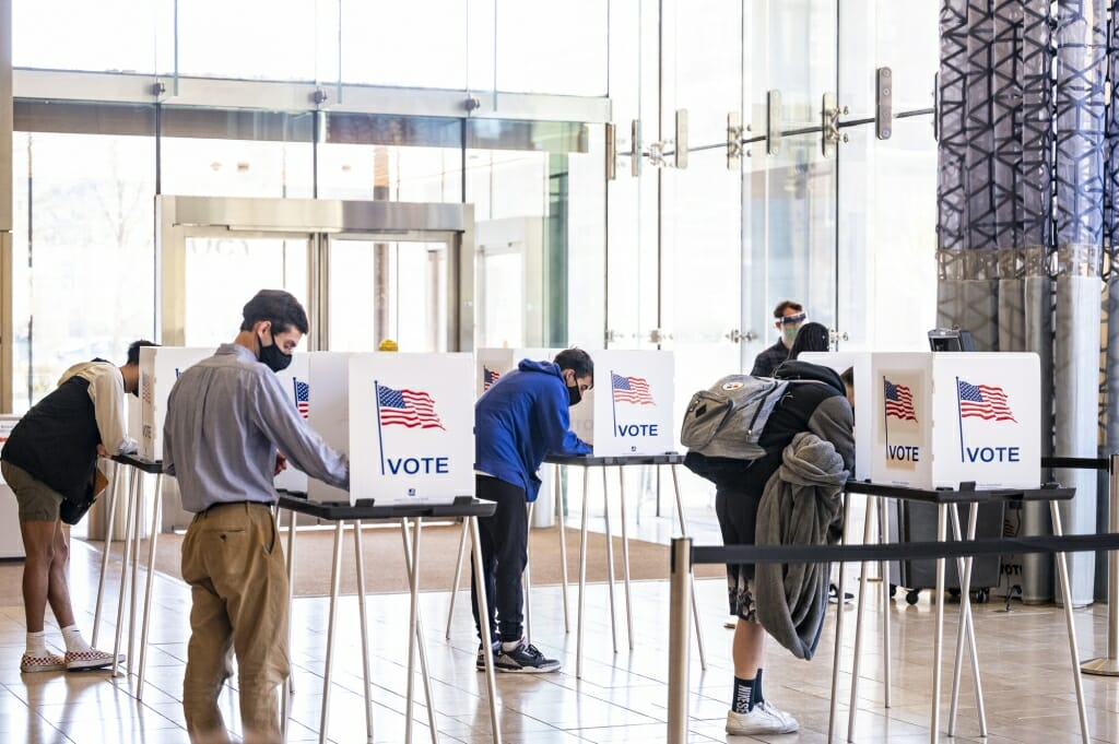 Students cast their ballots at physically distanced voting boxes at the Chazen Museum of Art polling station.