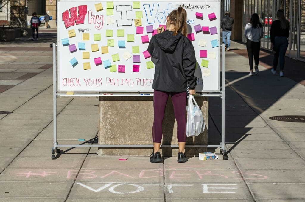 Students write down the reasons why they vote at an interactive display outside of 333 East Campus Mall.