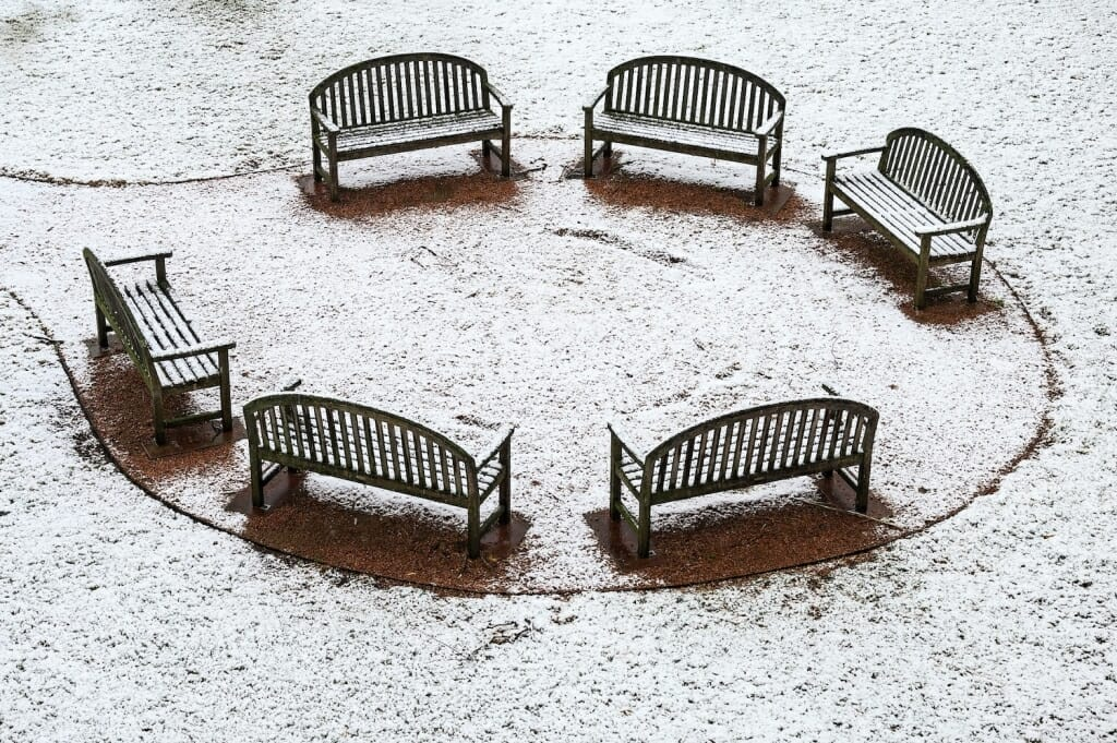 A circle of six empty benches near Vilas Hall are awaiting spring.