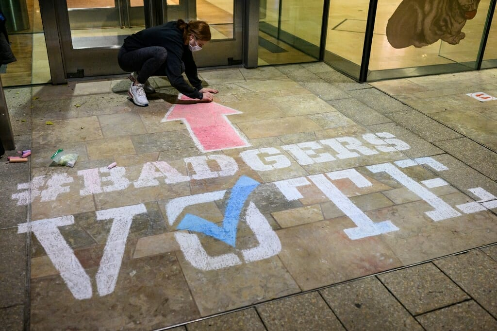 Student Gabi Runde finishes up a stenciled piece that points to the polling place.
