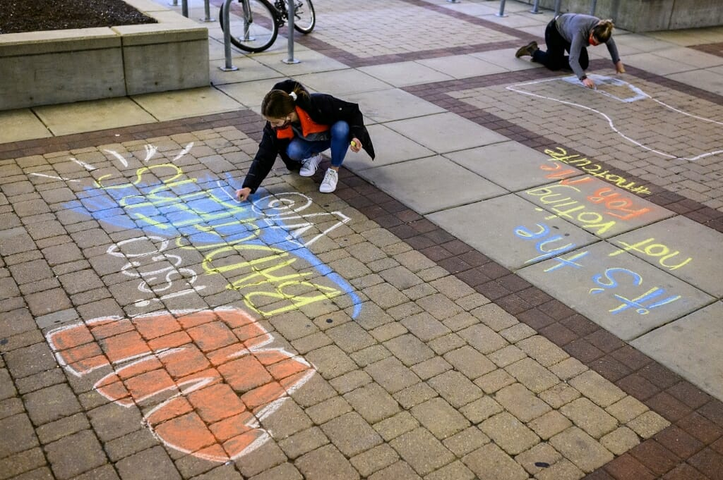 On Nov. 2, students Ellen Abad Santos (left) and Angela Maloney work with others in the #BadgersVote coalition to chalk messages on East Campus Mall.
